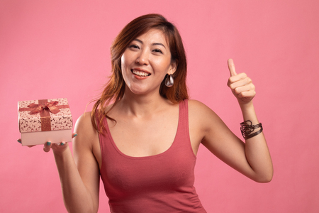 Asian woman thumbs up with a gift box on pink background