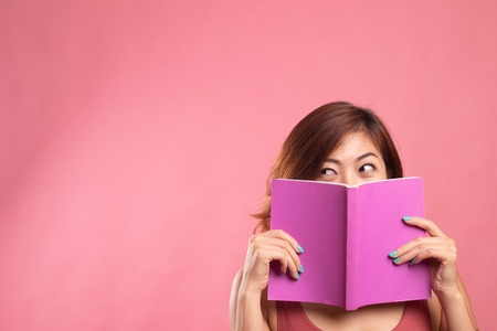 Young Asian woman with a book cover her face on pink background Banco de Imagens - 121442653