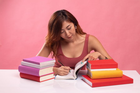 Young Asian woman read a book with books on table on pink background Banco de Imagens - 121442705