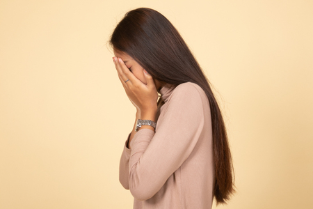 Sad young Asian woman cry with palm to face on beige background