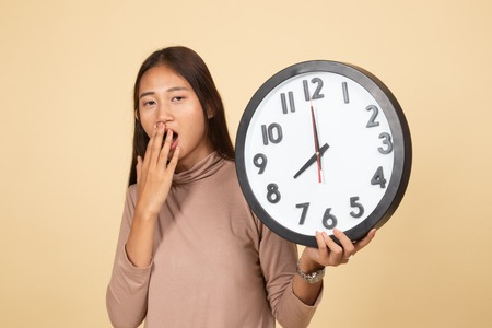 Sleepy young Asian woman with a clock in the morning  on beige background 스톡 콘텐츠