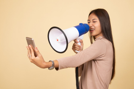 Angry  young Asian woman shout with megaphone to mobile phone  on beige background