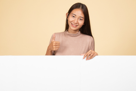 Young Asian woman show thumbs up with blank sign  on beige background 版權商用圖片