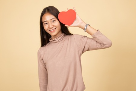 Asian woman with red heart  on beige background