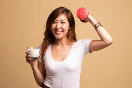 Healthy Asian woman drinking a glass of milk and dumbbell on beige background 版權商用圖片