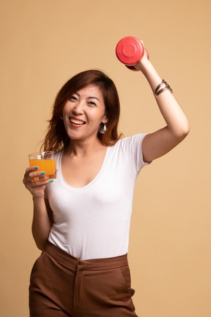 Young Asian woman with dumbbell drink orange juice on beige background 版權商用圖片