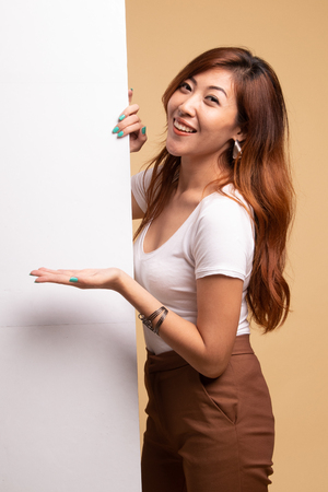 Young Asian woman present blank sign with palm hand on beige background