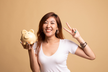 Asian woman show victory sign with pig coin bank on beige background