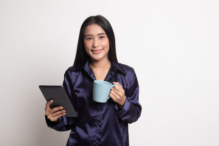 Young Asian woman with a computer tablet and coffee on white background Imagens