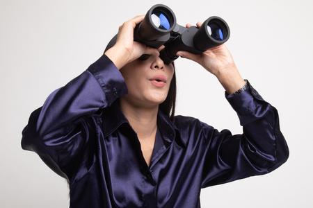 Jonge Aziatische vrouw met verrekijker op witte achtergrond