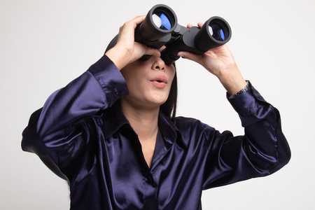 Young Asian woman with binoculars on white background