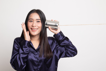 Happy Young Asian woman listen with tin can phone on white background