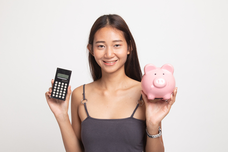 Asian woman with calculator and piggy bank on white background Banco de Imagens