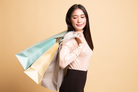 Young Asian woman happy with shopping bag on  beige background