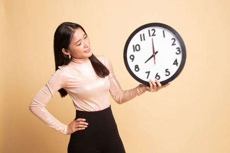 Young Asian woman with a clock on beige background Banque d'images