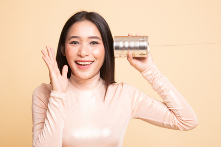Happy Young Asian woman listen with tin can phone on  beige background Stock fotó