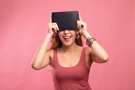 Young Asian woman with a computer tablet over her face on pink background