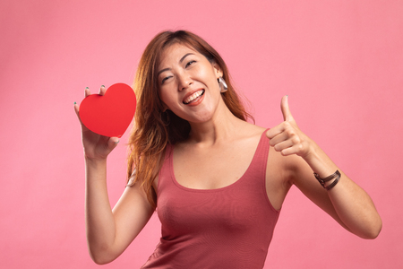 Asian woman thumbs up with red heart on pink background