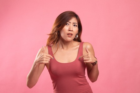 Young Asian woman point at herself ask why me on pink background