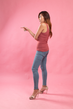 Full body side view of beautiful young asian woman pointing on pink background