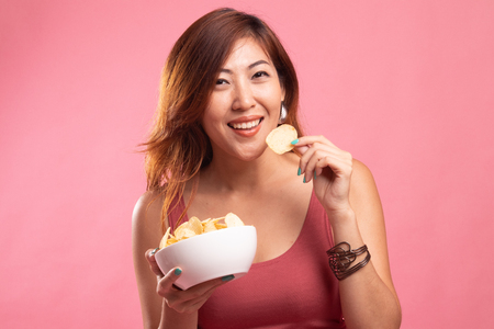 Young Asian woman eat potato chips on pink background Banco de Imagens