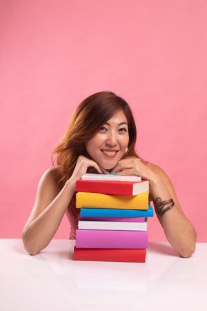 Happy young Asian woman read a book with books on table on pink background