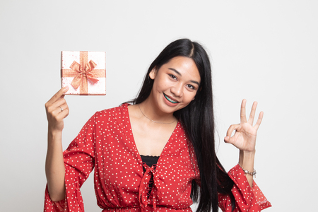 Young Asian woman show OK with a gift box on white background 版權商用圖片