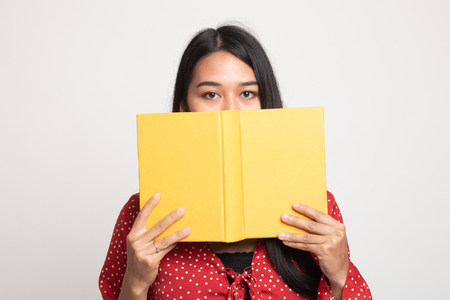 Young Asian woman with a book cover her face on white background Banco de Imagens - 121901686