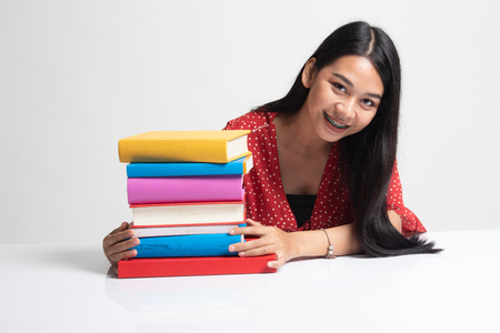 Happy young Asian woman read a book with books on table on white background