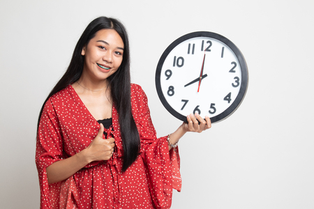 Young Asian woman thumbs up with a clock on white background