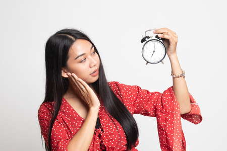 Young Asian woman is stressed with a clock on white background