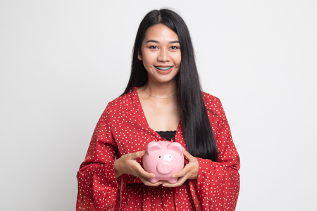 Young Asian woman with a pig coin bank on white background Banco de Imagens