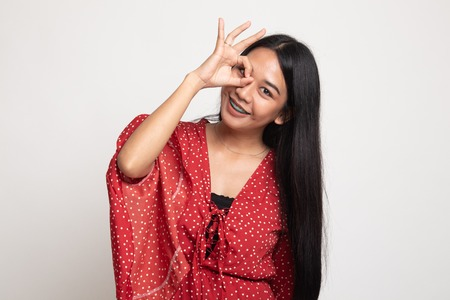 Beautiful young Asian woman show OK sign over her eye on white background