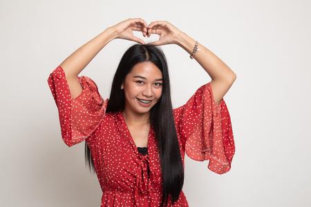 Junge asiatische Frau, die Herzhandzeichen auf weißem Hintergrund gestikuliert