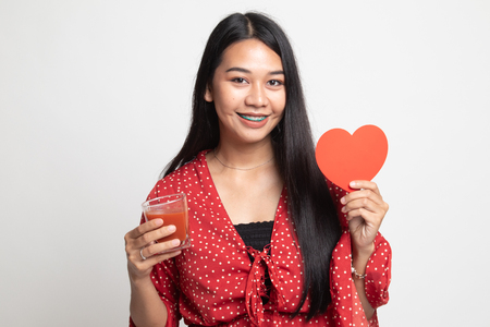 Young Asian woman with tomato juice and red heart on white background