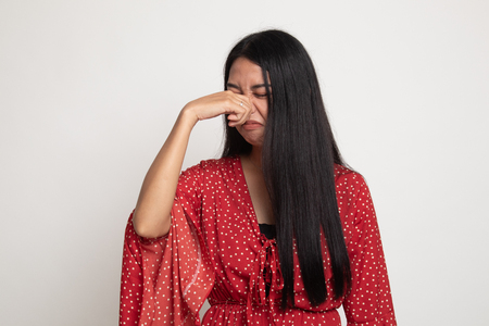 Young Asian woman holding her nose because of a bad smell on white background Imagens