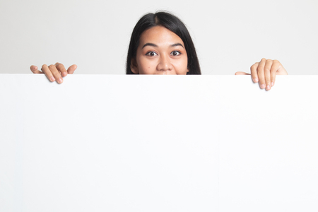 Close up of young Asian woman behind a blank sign on white background