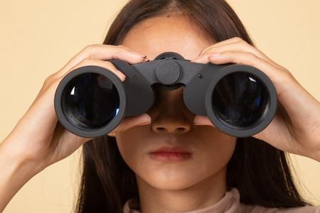 Joven asiática con binoculares sobre fondo beige