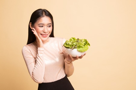 Healthy Asian woman with salad on  beige background 写真素材