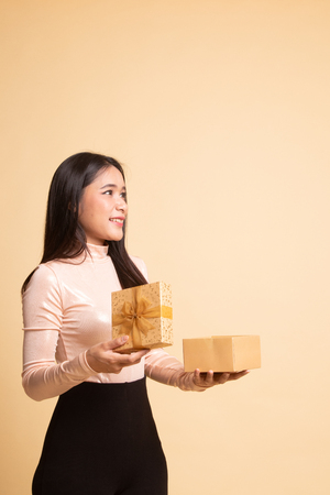 Young Asian woman open a gift box on  beige background 版權商用圖片