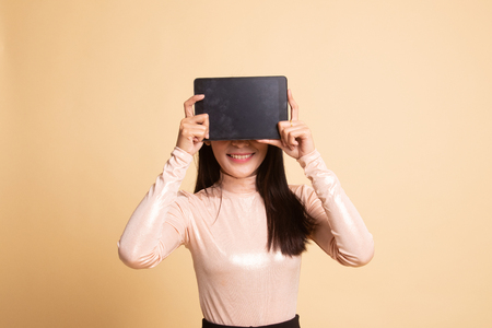 Young Asian woman with a computer tablet over her face on  beige background Banco de Imagens