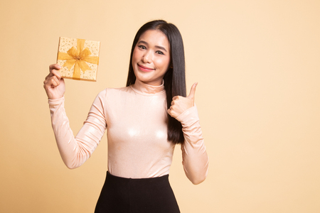 Young Asian woman thumbs up with a gift box on beige background