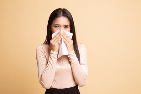 Young Asian woman got sick and flu on beige background Archivio Fotografico