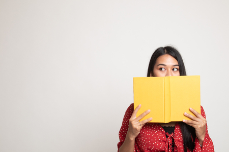 Young Asian woman with a book cover her face on white background Banco de Imagens - 122311211