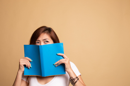 Young Asian woman with a book cover her face on beige background Banco de Imagens - 122322893