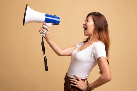 Beautiful young Asian woman announce with megaphone on beige background