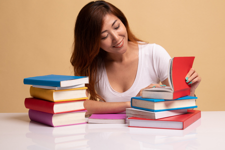 Young Asian woman read a book with books on table on beige background Stok Fotoğraf
