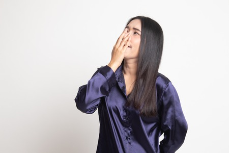 Sleepy young Asian woman yawn on white background