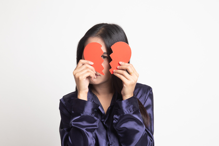 Beautiful young Asian woman with broken heart on white background 写真素材