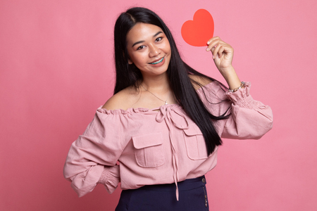 Asian woman with red heart on pink background